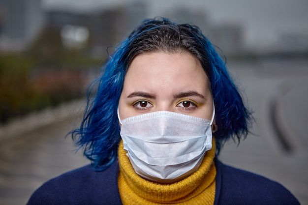 파란 머리를 가진 젊은 여성이 코로나 19로부터 보호하기 위해 의료 마스크에서 포즈를 취하고 있습니다.