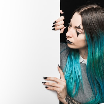 Young woman with blue hair looking at white board