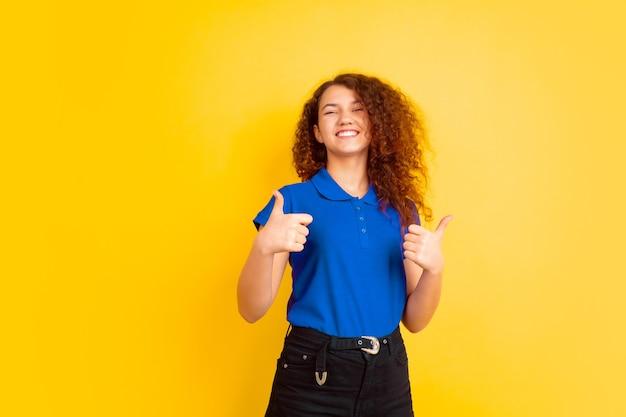 Молодая женщина с синей рубашкой поло и синими брюками дает большой палец вверх