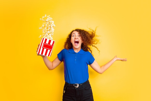 Young woman with blue polo shirt and blue trousers with popcorns