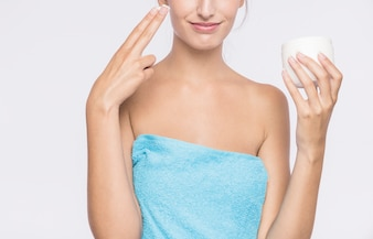 Young woman with body cream in towel