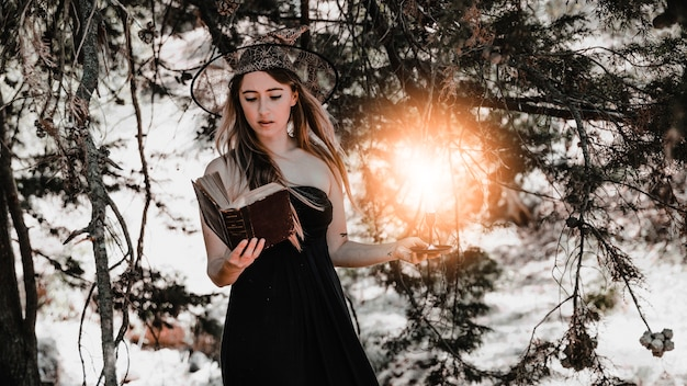 Young woman with book and candle standing in forest