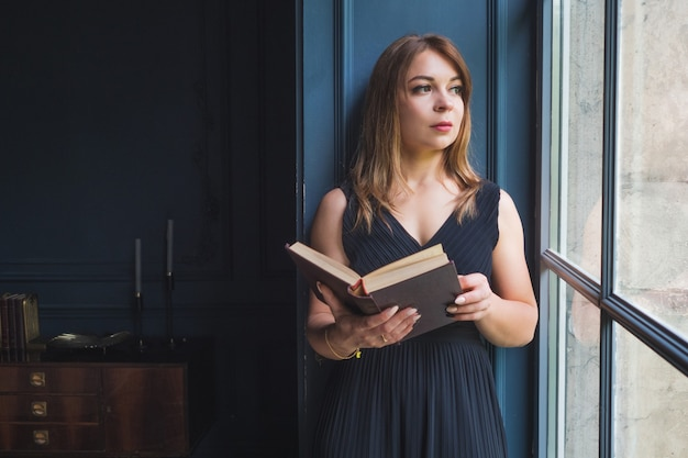 A young woman with a book in her hands is standing near the window.