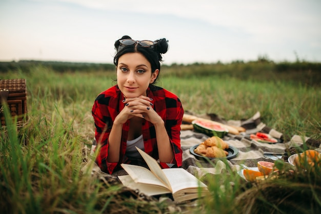 Young woman with book lies on plaid, picnic in summer field. romantic junket, happy holiday