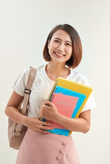 Young woman with books and backpack on white background