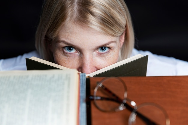 Young woman with books on a black background. close-up.