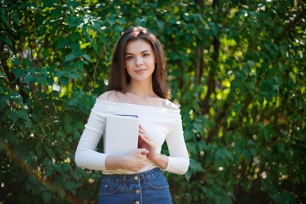 公園で本を持つ若い女性