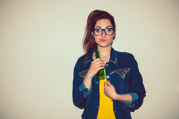 ビールと面白い顔のボトルを持つ若い女性
