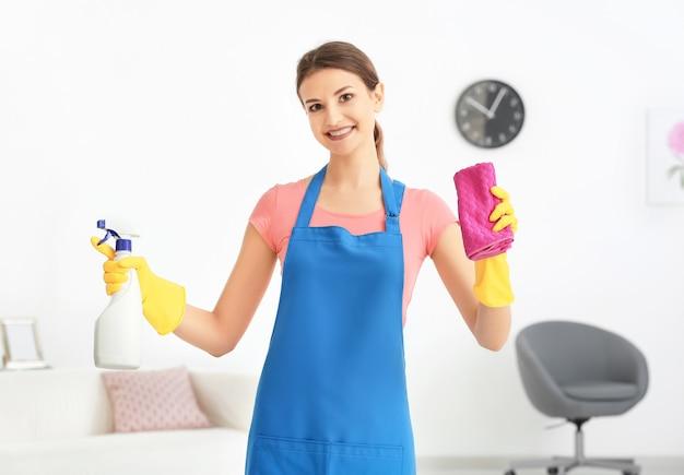 洗剤のボトルとフラットでぼろきれを持つ若い女性