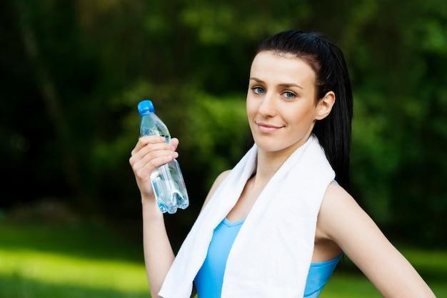 물 한 병을 가진 젊은 여자