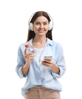 Young woman with bottle of water listening to music isolated
