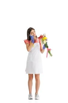 흰색 스튜디오 벽에 꽃다발을 든 젊은 여성