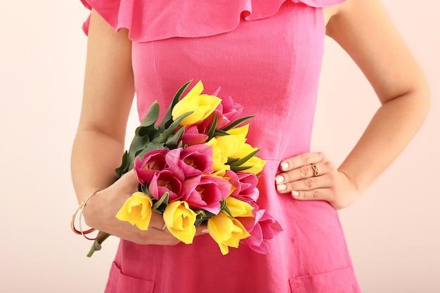ベージュの美しいチューリップの花の花束を持つ若い女性
