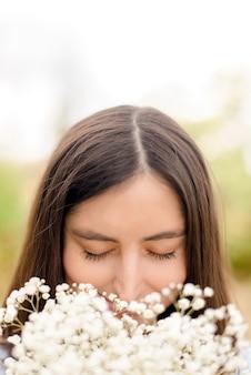 Молодая женщина с букетом цветов в парке