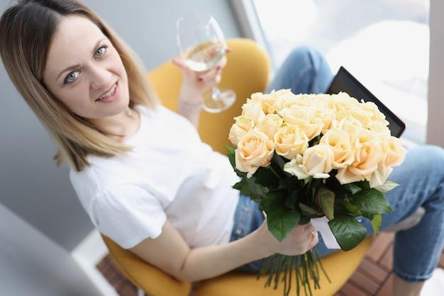 白ワインのガラスとラップトップに座っている茶バラの花束を持つ若い女性