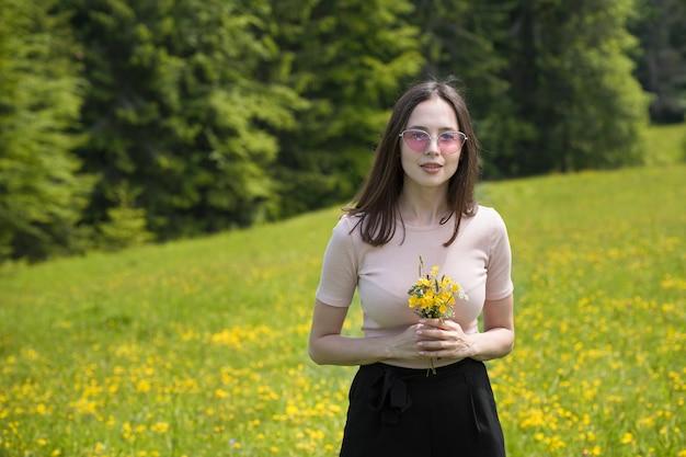 日当たりの良い芝生の上に野花の花束を持つ若い女性