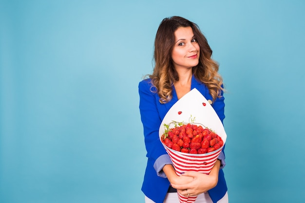 Young woman with a bouquet of strawberry