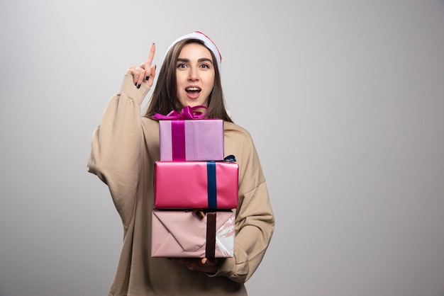 Young woman with boxes of christmas presents pointing up.