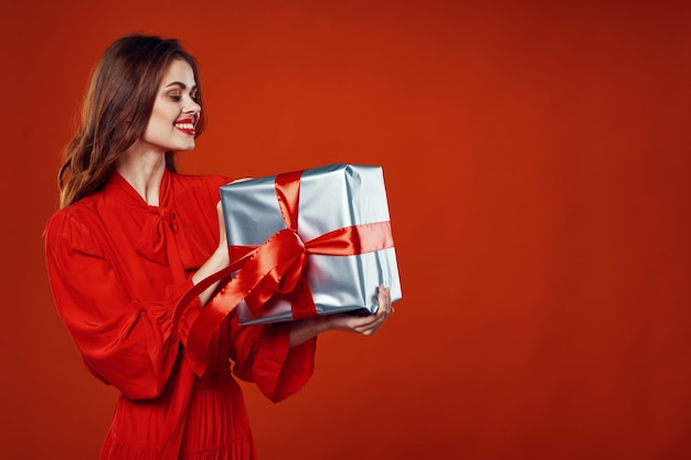 Young woman with boxes of gifts in her hands in the studio on a colored surface in beautiful clothes, selling gifts, happy christmas and new year