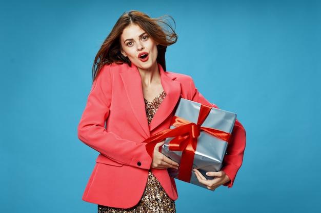 美しい服の着色された表面のスタジオで彼女の手に贈り物の箱を持つ若い女性、贈り物、幸せなクリスマスと新年を販売