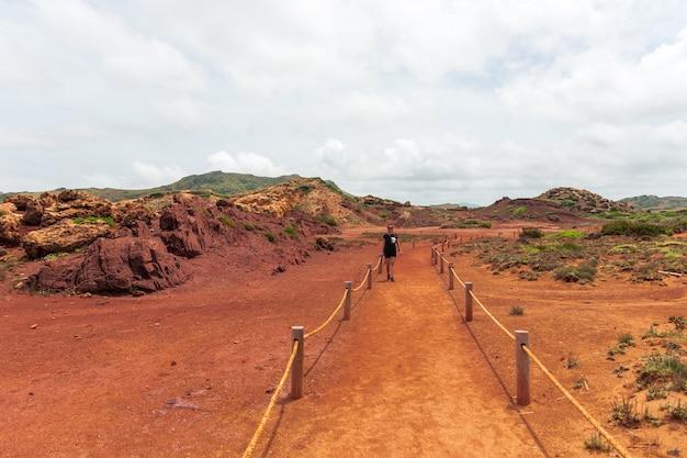 Молодая женщина с косами путешествует по вулканическому ландшафту на острове менорка.
