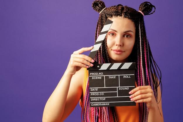 Молодая женщина с косами держит доску с хлопушкой крупным планом на фиолетовом фоне