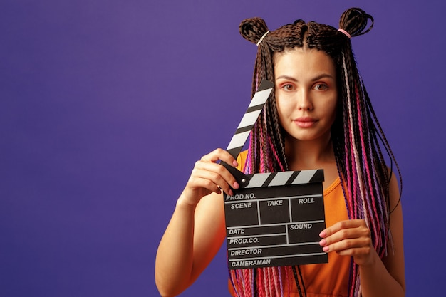 Молодая женщина с косами держит доску с хлопушкой крупным планом на фиолетовом
