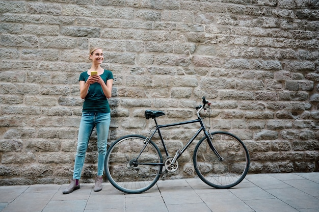 Young woman with brick wall behind her with bike and smartphone