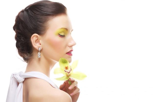 蘭を保持している明るいメイクを持つ若い女