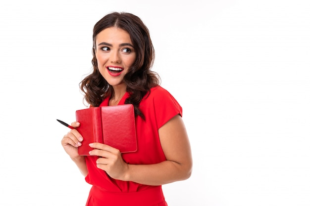A young woman with bright makeup, in a red summer dress stands with a notebook and smiles