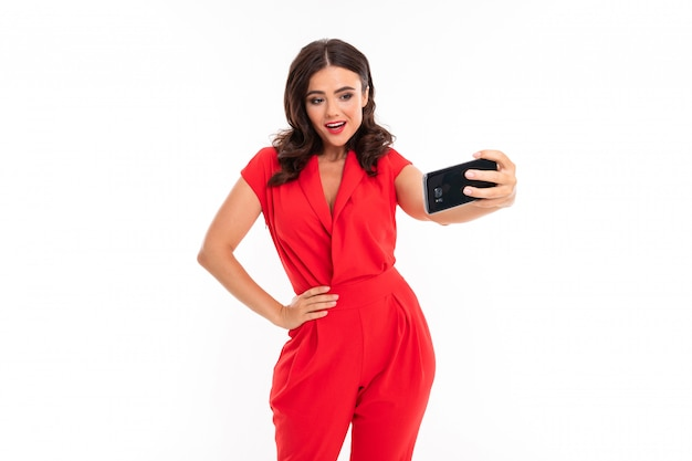 A young woman with bright makeup, in a red summer dress stands with a phone in hand and do selfie