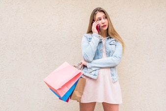 Young woman with bright shopping bags talking by phone