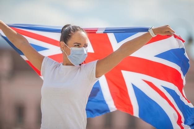 영국 국기를 가진 젊은 여성이 야외에서 마스크를 쓰고 있습니다.
