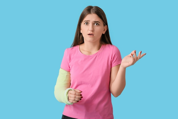 색상에 부러진 된 팔을 가진 젊은 여자