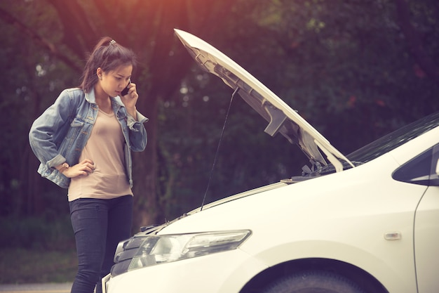 Young woman with broken car calling for help.vintage color