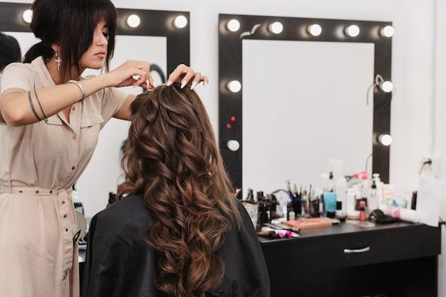 뷰티 살롱에서 갈색 곱슬 긴 머리를 가진 젊은 여자
