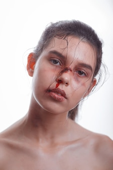 Young woman with bruises on face victim of domestic violence on white