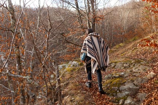 ポンチョでブルネットの髪の若い女性は秋の森の中を歩く