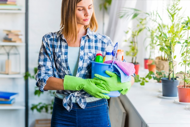 Young woman with bucket of cleaning equipments