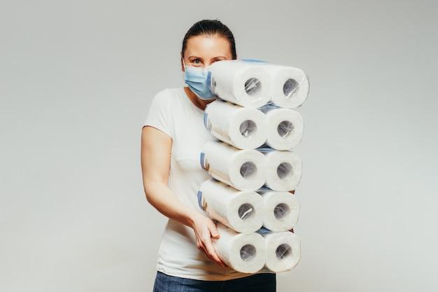 Молодая женщина с большей частью пакетов туалетной бумаги.