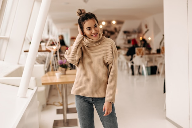 Young woman with bun and dressed in beige sweater and dark denim pants posing in cafe