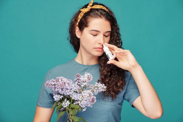 Молодая женщина с букетом сирени распыляет противоаллергическое лекарство в нос, стоя перед камерой у синей стены