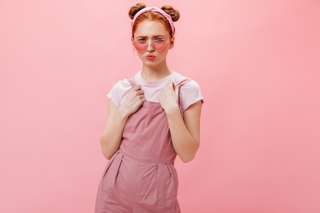 ピンクの背景にポーズをとるパンを持つ若い女性。スタイリッシュなメガネ、ピンクのジャンプスーツ、白いトップスの女性の肖像画。