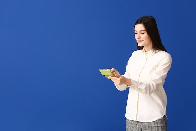 色の計算機を持つ若い女性