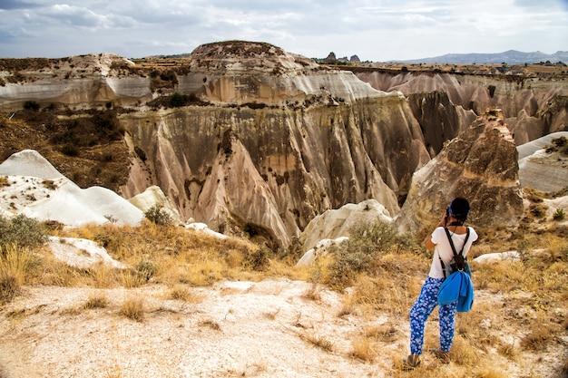 Молодая женщина с камерой и рюкзаком фотографируя на cappadocia, турции.