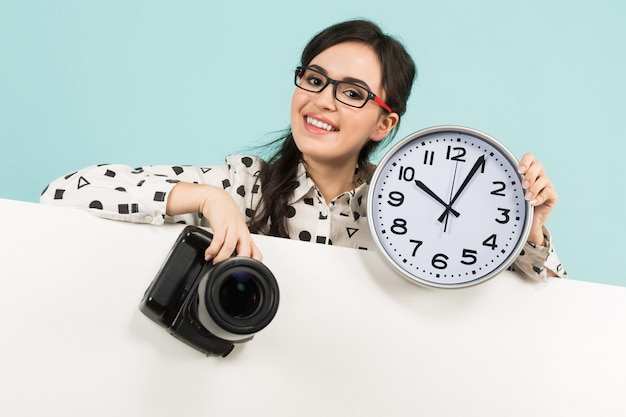 Young woman with camera and clocks