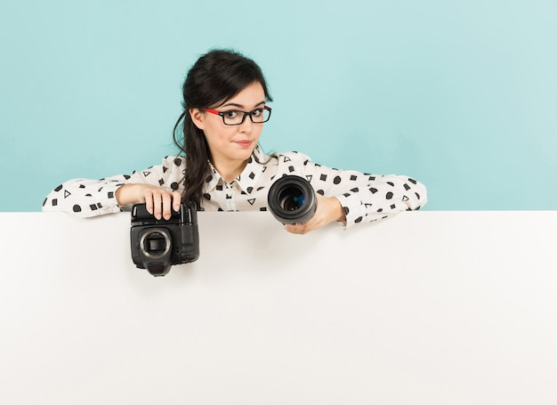 Young woman with camera and lens