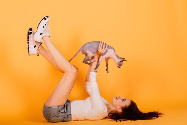 スタジオ、灰色の背景でカナダのスフィンクス猫と若い女性
