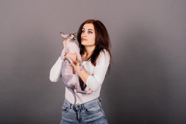 Young woman with canadian sphynx cat in studio, grey background