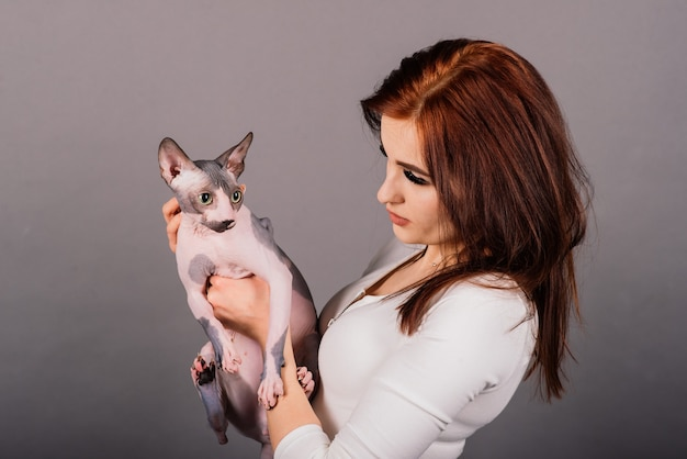 Young woman with canadian sphynx cat in a studio, grey background